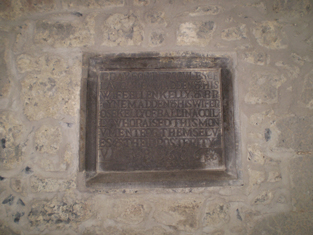 Plaque to north elevation of nave.